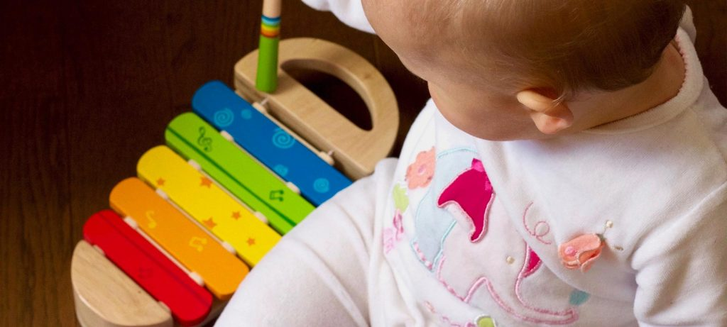 baby playing with colourful wooden xylophone